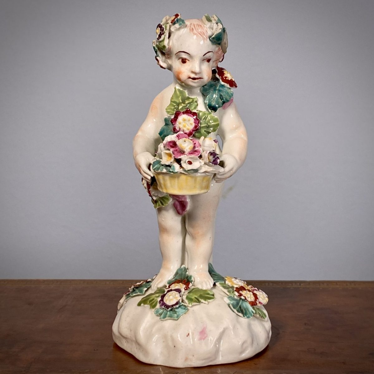 C18th Derby Figure of a Putto Holding a Basket of Flowers